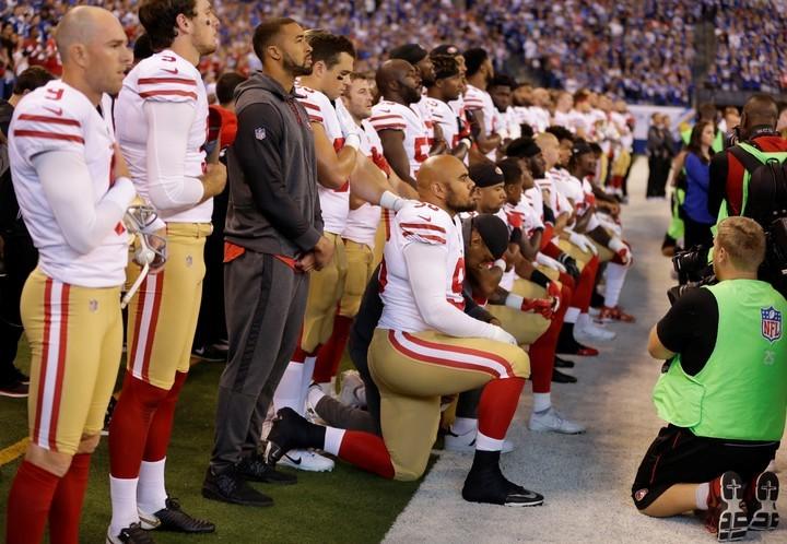 Jugadores de San Francisco 49ers permanecen arrodillados en el campo de juego.