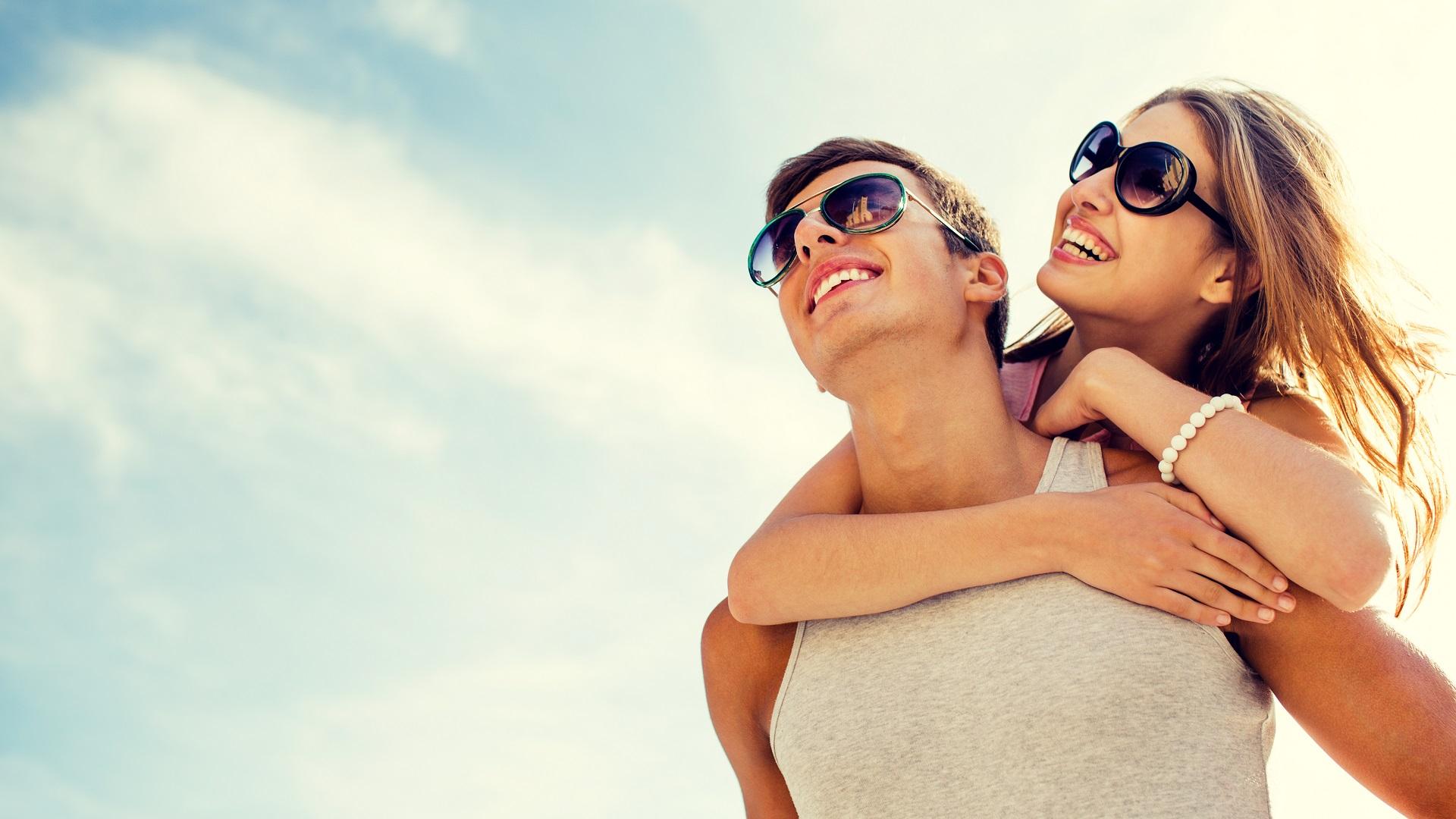 mujer-con-lentes-oscuros-abrazando-por-la-espalda-a-hombre-con-lentes-similares