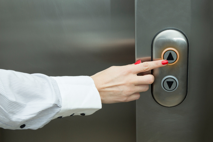 : Woman pressing the elevator button with her forefinger.
