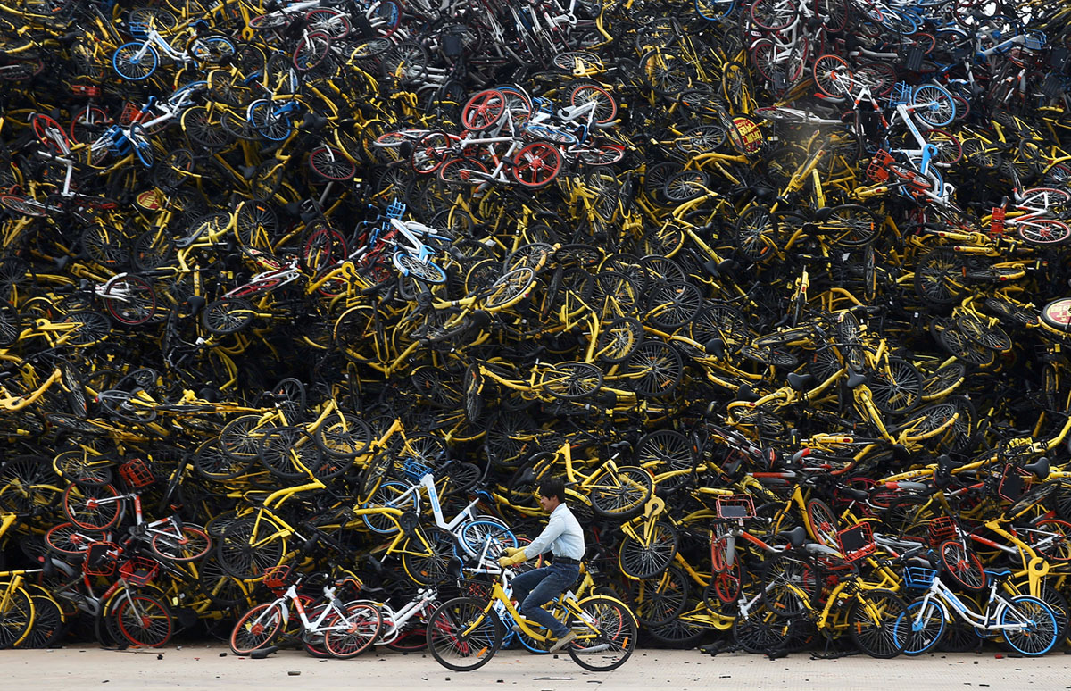 Worker rides a shared bicycle past piled-up shared bikes at a vacant lot in Xiamen